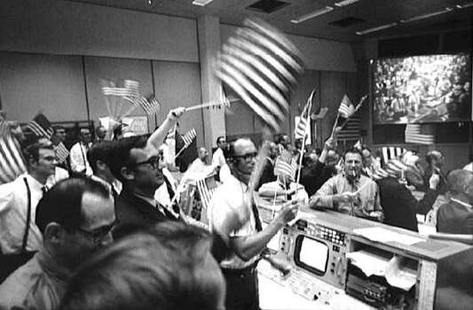 Misson control personnel wave flags to celebrate the the return to earth of Apollo 11 on July 24, 1969. Photo: NASA, NYT