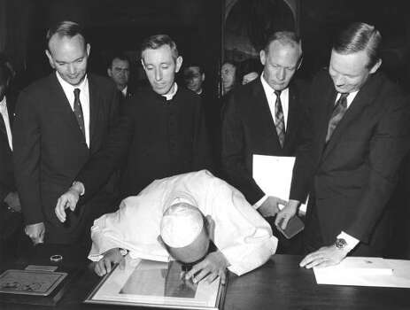Pope Paul VI looks through a magnifying lens as he examines a microfilm of messages from world leaders, brought to the moon by the Apollo 11 astronauts, during an audience in the pontiff`s private studio for them and their wives, Oct. 16, 1969. Standing behind the Pope, in front row, are (l/r:) Michael Collins; Msgr. P. Conveney, acting as interpreter; Edwin Aldrin and Neil Armstrong. Photo: Anonymous, ASSOCIATED PRESS