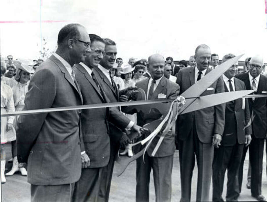"""The suburban Clear Lake area grew along with NASA's Manned Aircraft Center, later to be called Johnson Space Center. In this 1963 photo, Texas Gov. John Connally uses giant scissors to  snip the ribbon on a new development project called Clear Lake City. Two years later, a Clear Lake City brochure boasted that 5,500 people were employed at the space center and pointed out that """"employees are happier working in pleasant surroundings than on industrial row."""" Today nearly 17,000 people work for NASA or one of its contractors. Photo: Chronicle"""