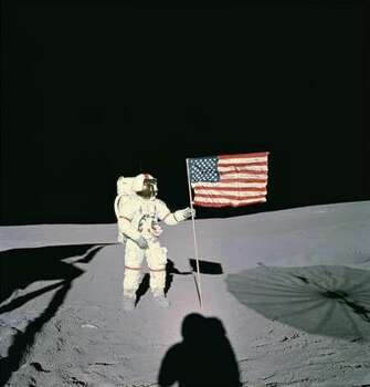 Astronaut Alan B. Shepard stands with the American Flag on the lunar surface in this February 1971 file photo. Shepard was the first American to fly in space and the fifth human to walk on the moon. Photo: AP File