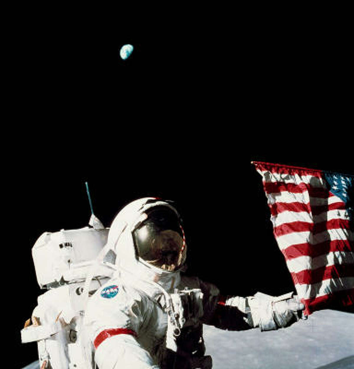 Astronaut Gene Cernan was a member of Apollo 17 in 1972. He is shown here, with the Earth rising in the background, holding an American flag.
