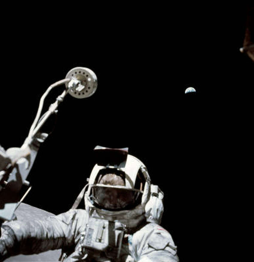 Harrison Jack Schmitt on the moon with tool raised and Earth on the rise in the background.