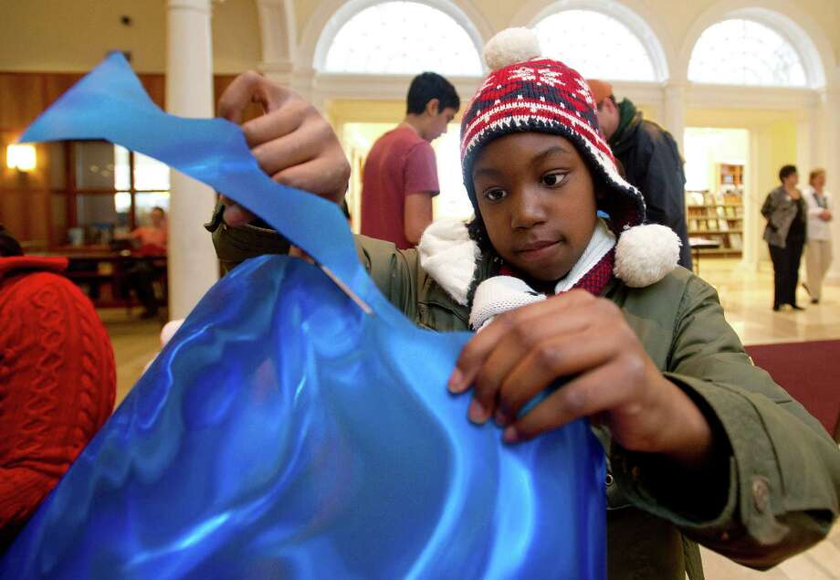 Madison Williams, 9, cuts a piece of polycarbonate film into the shape of a wave on Saturday, March 29, 2014. The strings of wave shapes were hung at the Ferguson Library in a community art project to celebrate water and to accompany water-themed programs at the library. Photo: Lindsay Perry / Stamford Advocate