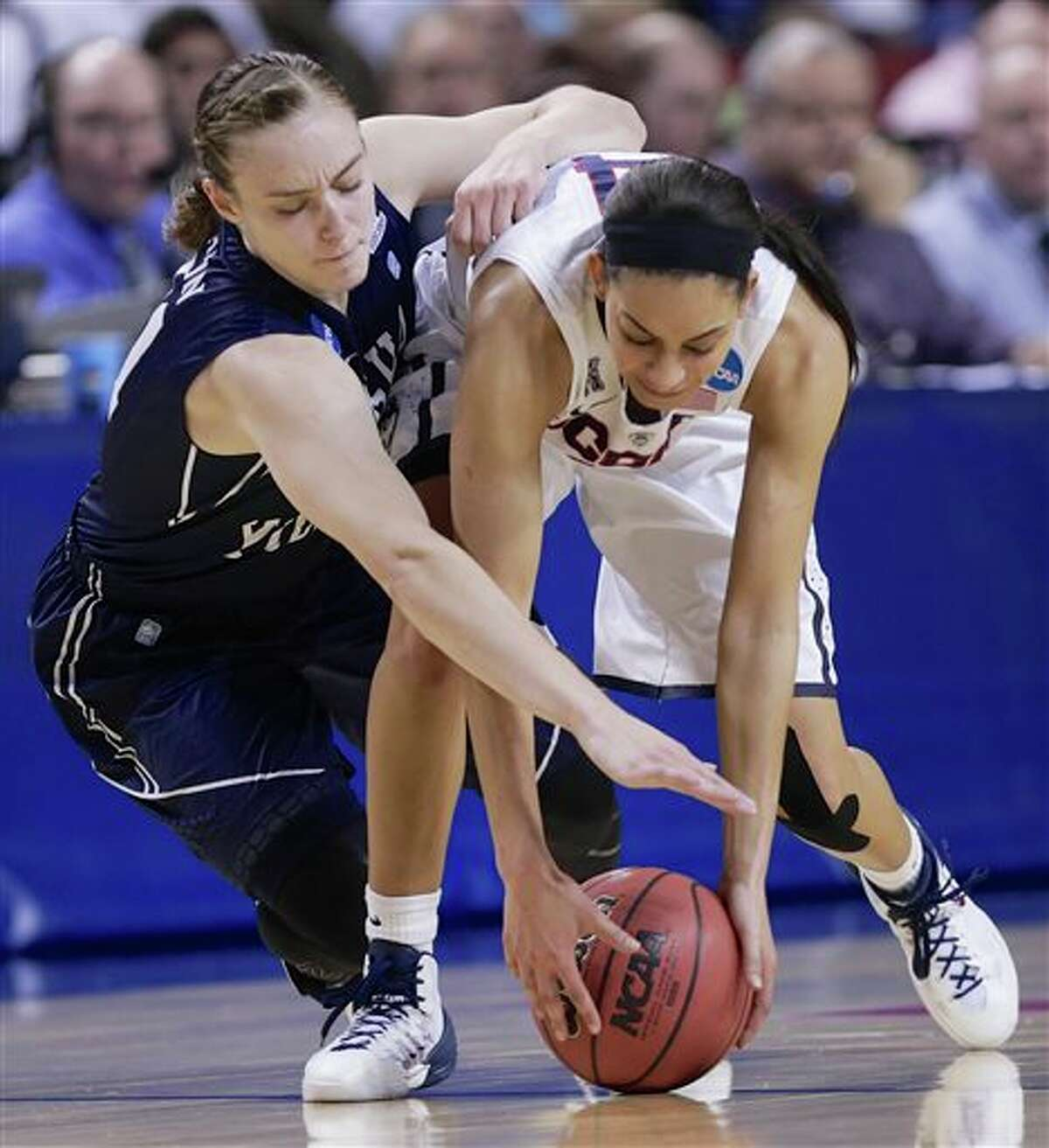 BYU's Lexi Eaton, left, and Connecticut's Bria Hartley (14) scramble for the ball during the first half of a regional semifinal in the NCAA college basketball tournament in Lincoln, Neb., Saturday, March 29, 2014. (AP Photo/Nati Harnik)