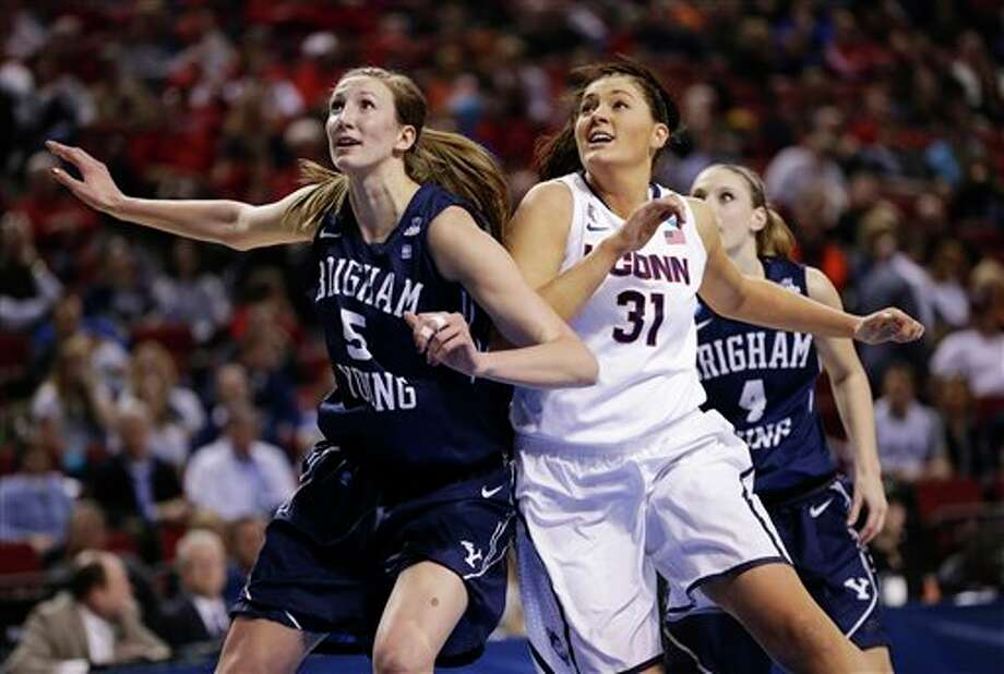 BYU's Jennifer Hamson (5) and  Kim Beeston (4), jockey for position against Connecticut's Stefanie  Dolson (31)  during the first half of a regional semifinal in the NCAA  college basketball tournament in Lincoln, Neb., Saturday, March 29,  2014. (AP Photo/Nati Harnik)