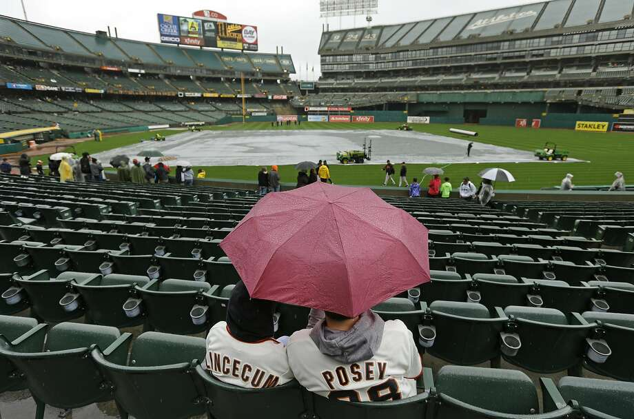 Two Giants fans seek cover from the rain while waiting for the finale of the three-game Bay Bridge Series between the A's and Giants in Oakland on Saturday afternoon. Photo: Ben Margot, Associated Press
