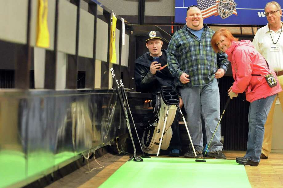 Cindy Shafer of Valatie, second from right, watches her putt at the Putt 4 PAL game to benefit the Albany Police Athletic League during the Empire Golf Expo on Saturday, March 29, 2014, at the Convention Center in Albany, N.Y. Joining her, from left are, her friend James McDarby, her husband Tal Shafer and volunteer Joe Scesny. The expo continues Sunday from 11 a.m. to 4 p.m. (Cindy Schultz / Times Union) Photo: Cindy Schultz / 00026308A