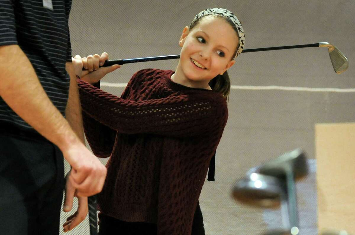 Schuyler Lorette, 12, of East Greenbush, right, receives works on her swing with Schuyler Meadows golf pro Bob Van Auken during the Empire Golf Expo on Saturday, March 29, 2014, at the Convention Center in Albany, N.Y. The expo continues Sunday from 11 a.m. to 4 p.m. (Cindy Schultz / Times Union)