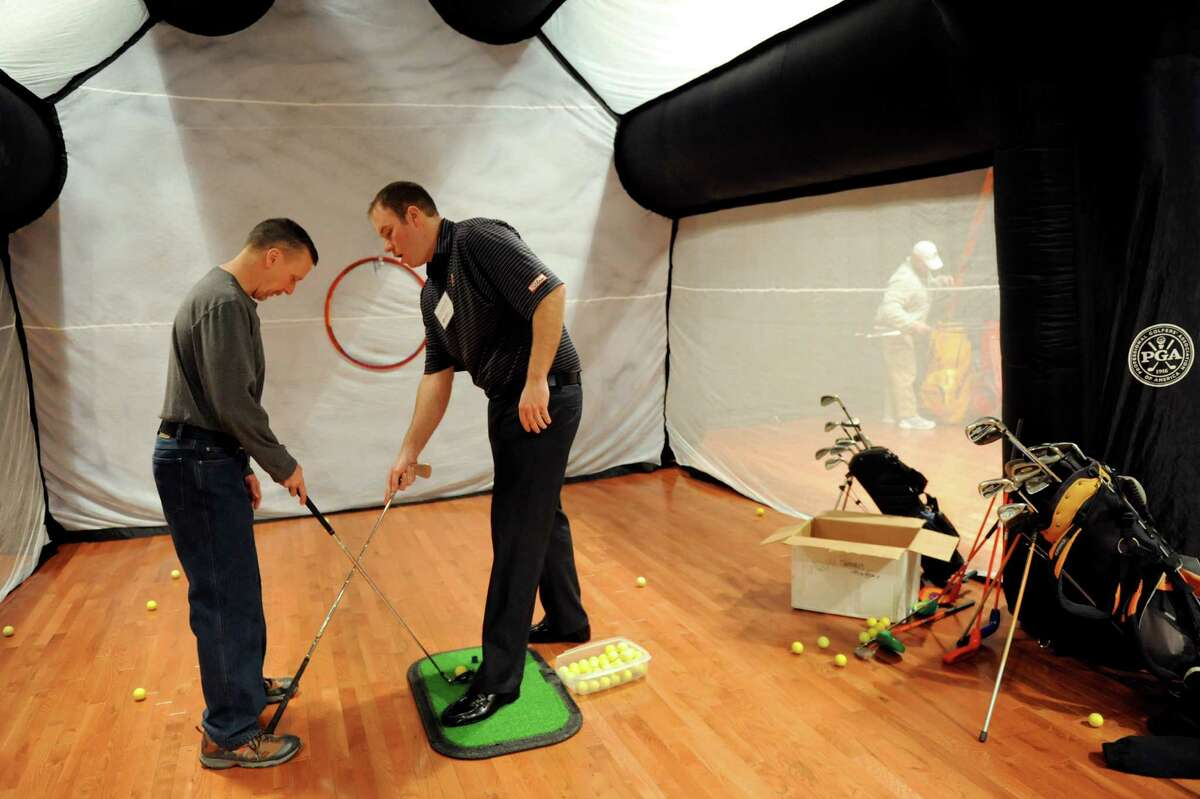 Chris Hammond of Rotterdam, left, receives a free lesson from Schuyler Meadows golf pro Bob Van Auken during the Empire Golf Expo on Saturday, March 29, 2014, at the Convention Center in Albany, N.Y. The expo continues Sunday from 11 a.m. to 4 p.m. (Cindy Schultz / Times Union)