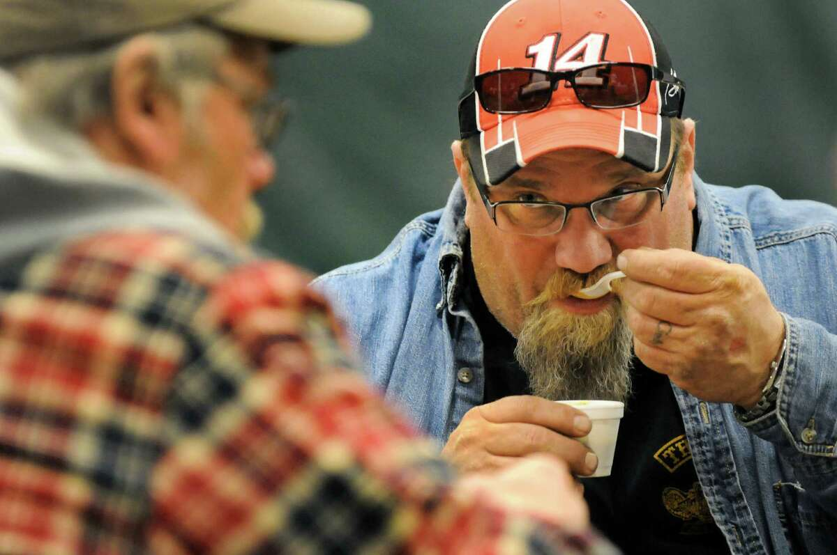Jeff Wright of Guilderland samples chili during the 3rd annual Chili Cook-Off to benefit the David Fisher Upper Hudson Heroes Kayak team of Watervliet on Saturday, March 29, 2014, at the Watervliet Dome in Watervliet, N.Y. Joining him is Rick Bruhns of Averill Park. The not-for-profit organization offers disabled veterans the opportunity to develop their physical & emotional capabilities through the sport of kayaking. (Cindy Schultz / Times Union)