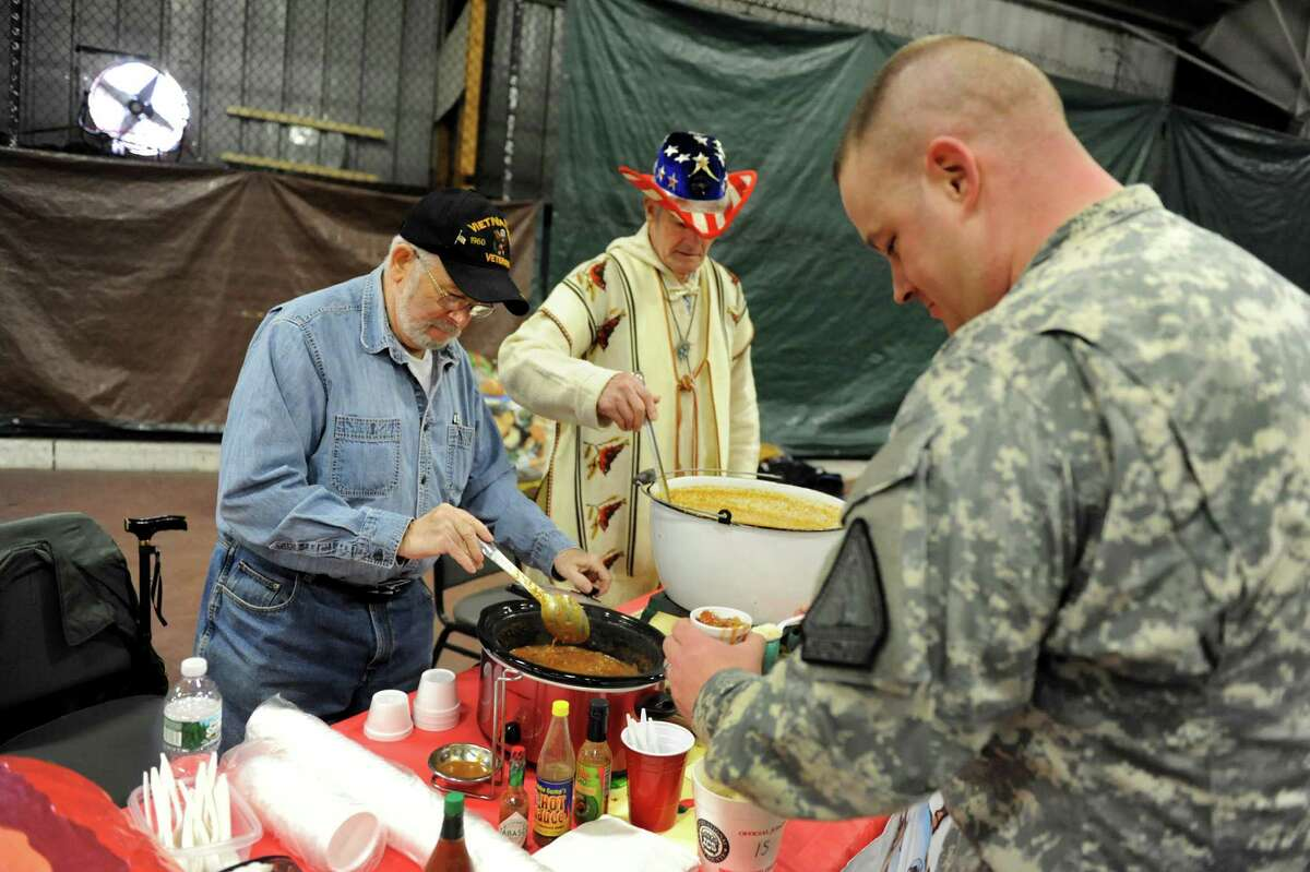 SFC James Montesano of the National Guard, right, gets a sampling of chili during the 3rd annual Chili Cook-Off to benefit the David Fisher Upper Hudson Heroes Kayak team of Watervliet on Saturday, March 29, 2014, at the Watervliet Dome in Watervliet, N.Y. Serving up the chili, sponsored by Salty's Pub and Bistro, is Vietnam veteran Bill Carter, left, and Ed Duclos, who served in the Marines. (Cindy Schultz / Times Union)
