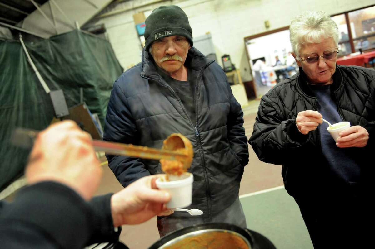 Edward Thompson, center, and his neighbor Sharon Batto of Watervliet get a sampling of chili from Deacon Blues during the 3rd annual Chili Cook-Off to benefit the David Fisher Upper Hudson Heroes Kayak team of Watervliet on Saturday, March 29, 2014, at the Watervliet Dome in Watervliet, N.Y. The not-for-profit organization offers disabled veterans the opportunity to develop their physical & emotional capabilities through the sport of kayaking. (Cindy Schultz / Times Union)