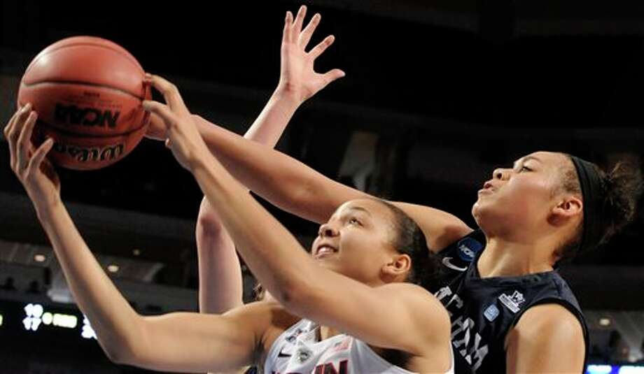 Connecticut's  Stefanie Dolson, left, takes a shot in front of BYU's Morgan Bailey  during the second half of a regional semifinal in the NCAA women's  college basketball tournament Saturday, March 29, 2014, in Lincoln, Neb.  Connecticut won 70-51. (AP Photo/Dave Weaver)