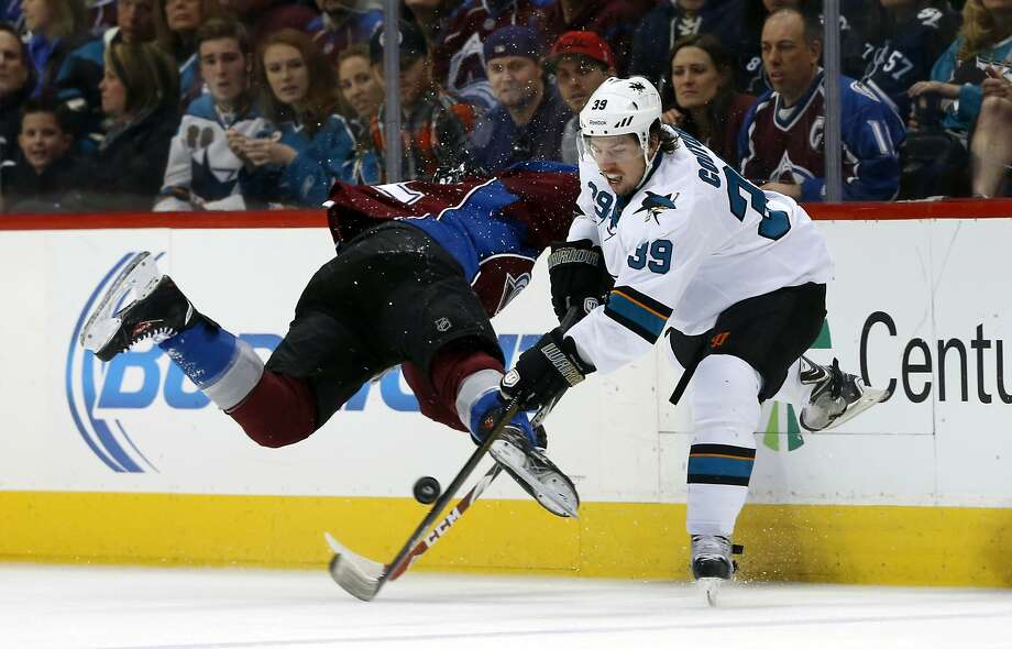 Sharks forward Logan Couture sends Avalanche left wing Gabriel Landeskog into the boards while battling for the puck. Photo: David Zalubowski, Associated Press