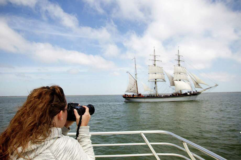 Christa Schreckengost takes photos of the 1877 tall ship Elissa as she sets sail for the first time in more than four years Saturday, March 29, 2014, in Galveston. Elissa once again returned to the open waters of the Gulf of Mexico with guests and supporters aboard for a first hand look at her completed restoration. Photo: Brett Coomer, Houston Chronicle / © 2014 Houston Chronicle