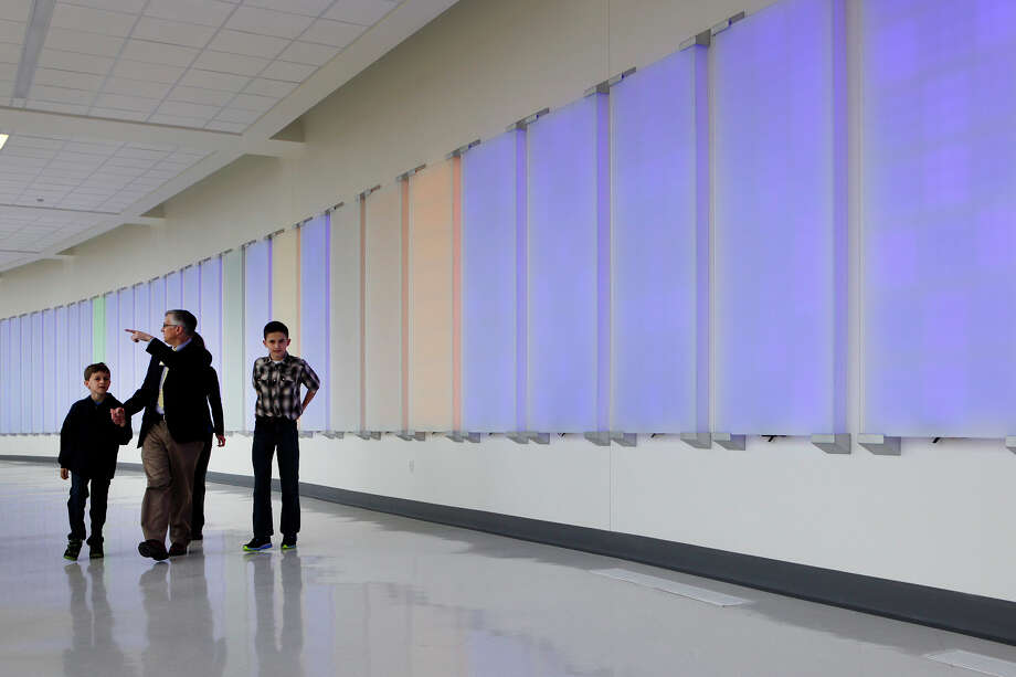 "Bryan Alsip, the executive vice president and chief medical officer for University Hospital, shows his wife and children, Brandon (left) and Matthew the view from the staff hallway of the University Hospital's Sky Tower March 29, 2014 as the artwork titled ""You Activate This Space"" by Ansen Seale changes colors as they walk by. After the ribbon cutting for the new 10-story building took place the public was allowed to take tours throughout the hospital. Photo: Cynthia Esparza, For The Express-News / FOR THE SAN ANTONIO EXPRESS-NEWS"