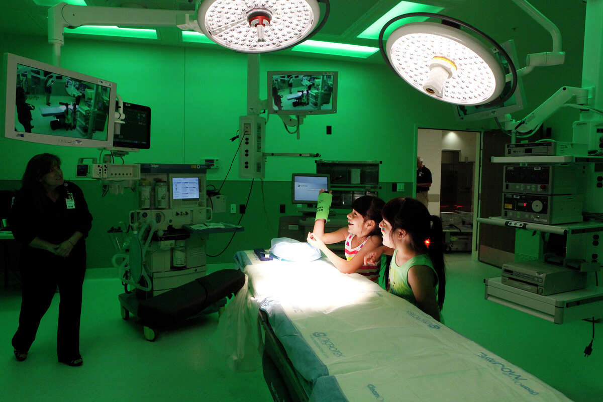 Twins Megan (left) and Alexis Rodriguez, 8, watch themselves on the monitors in one of the operating rooms March 29, 2014 at University Hospital's Sky Tower as they asked questions while touring the facility. There are 35 operating rooms in the Sky Tower.