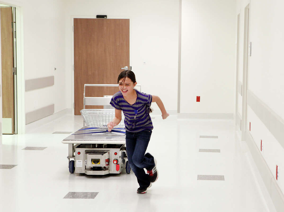 Emily Agans, 10 runs away from the Automated Guided Vehicle March 29, 2013 as she was seeing if it would stop if she got in front of it during a tour of University Hospital's Sky Tower. The Automated Guided Vehicle is a robot that will go between operating rooms as well as other places in the hospital and drop off and pick up supplies to the rooms that need it and is guided by the color squares on the floor which have magnets underneath them.