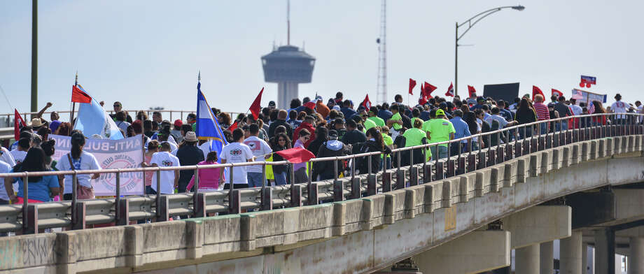 Peoiple cross the Guadalupe St. bridge during the Cesar Chaves March Saturday. Photo: Robin Jerstad