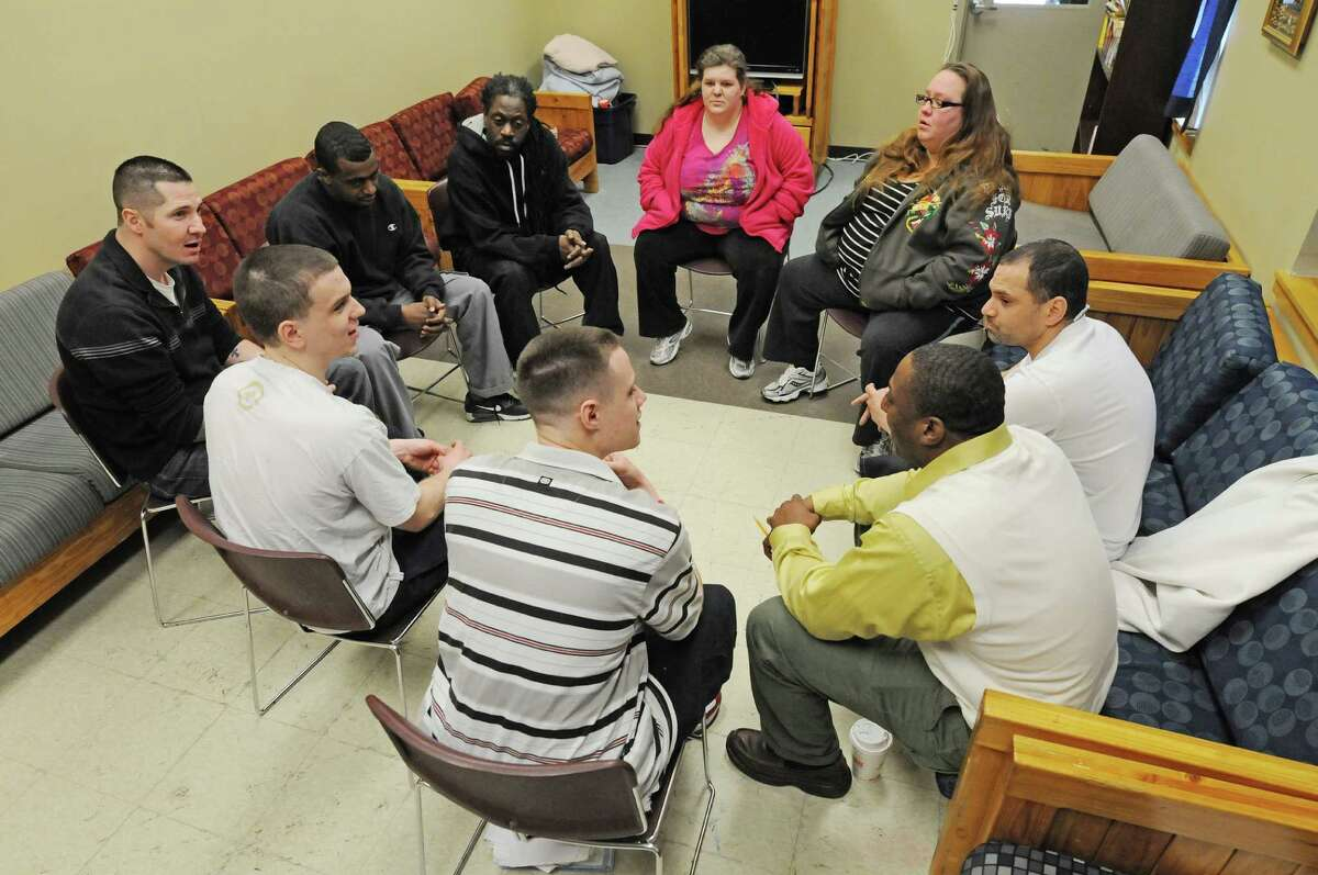 Hope House assistant manager, Kyron Stevenson, foreground right, leads a group therapy session for residents on Monday, March 24, 2014, in Albany, N.Y. (Paul Buckowski / Times Union)