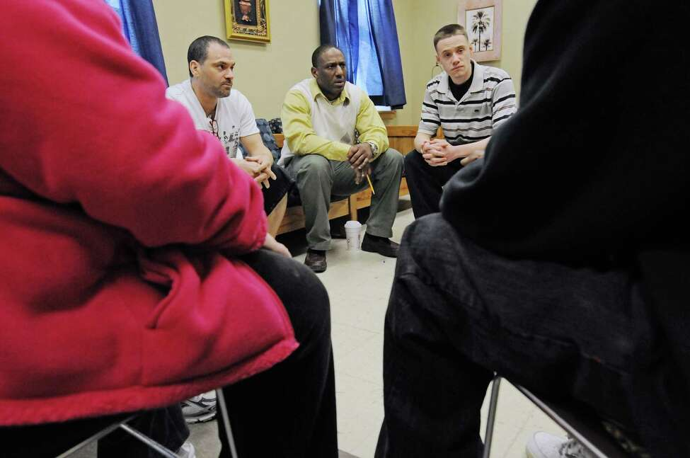 Hope House assistant manager, Kyron Stevenson, background center, leads a group therapy session for residents on Monday, March 24, 2014, in Albany, N.Y. (Paul Buckowski / Times Union)
