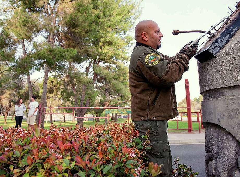 Orange County Parks grounds keeper Frank Amaro removes the supports to the sign at the entrance of Ralph B. Clark Regional Park in Buena Park in Fullerton, Calif.,  on Saturday, March 29, 2014,  morning after rangers discovered it fell off it's supports after an earthquake hit Orange County Friday night.   More than 100 aftershocks have rattled Orange County south of Los Angeles where a magnitude-5.1 earthquake struck Friday.  Despite the relatively minor damage, no injuries have been reported. (AP Photo/The Orange County Register, Ken Steinhardt)   MAGS OUT; LOS ANGELES TIMES OUT   ORG XMIT: CAANR201 Photo: KEN STEINHARDT, / The Orange County Register