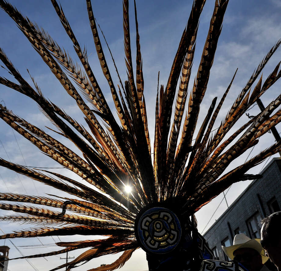 The headdress of Rey Rios is highlighted by the rising sun prior to the start of the Cesar Chavez March Saturday. Photo: Robin Jerstad