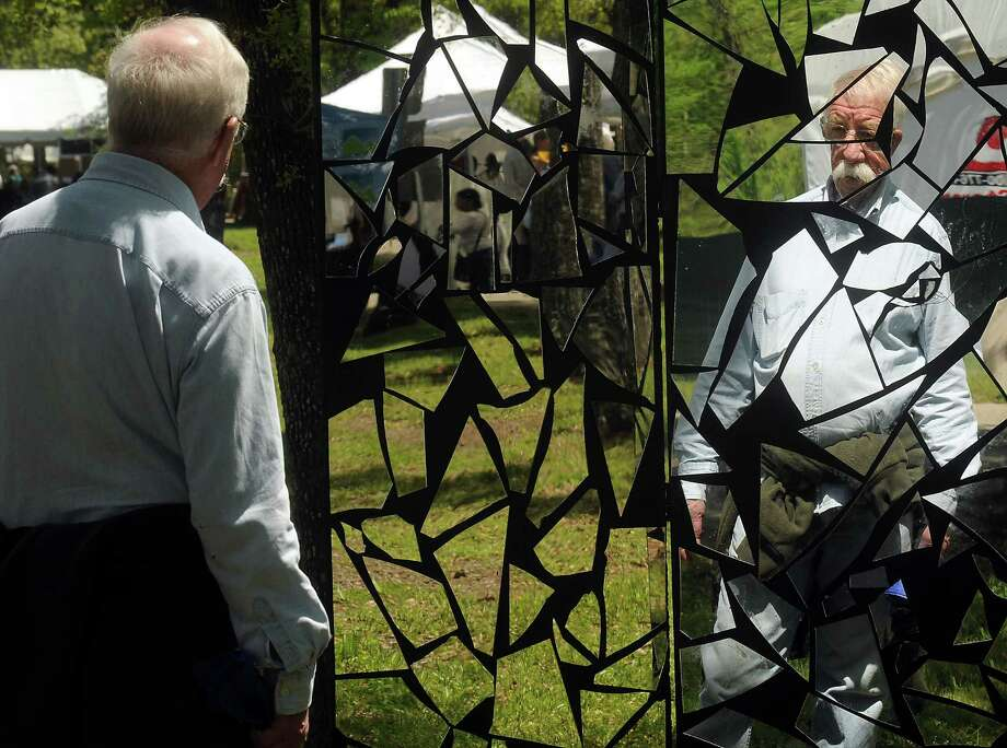 Kelly Harlan looks at a piece by Taylor Smith at the Bayou City Art Festival at Memorial Park Saturday March 29, 2014. Photo: Dave Rossman, For The Houston Chronicle / Freelance