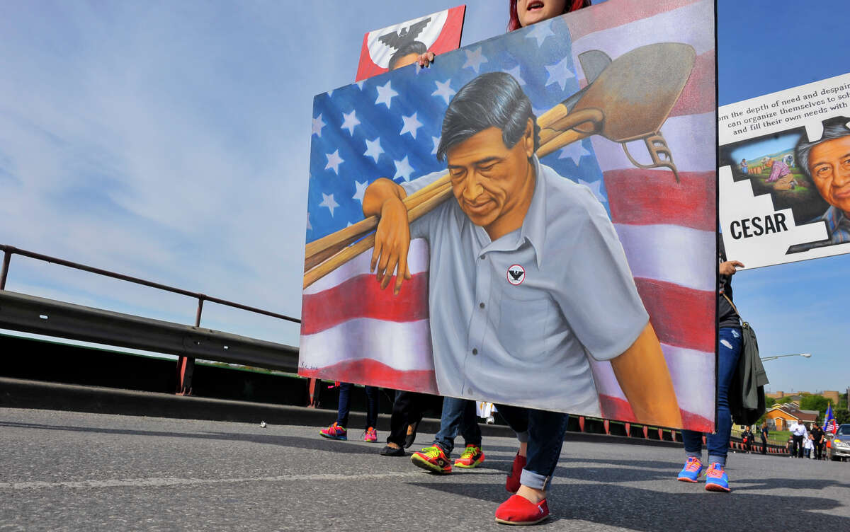 A poster of Cesar Chavez is carried at the head of the Cesar Chavez March as it makes it's way up the Guadalupe St. bridge Saturday morning.