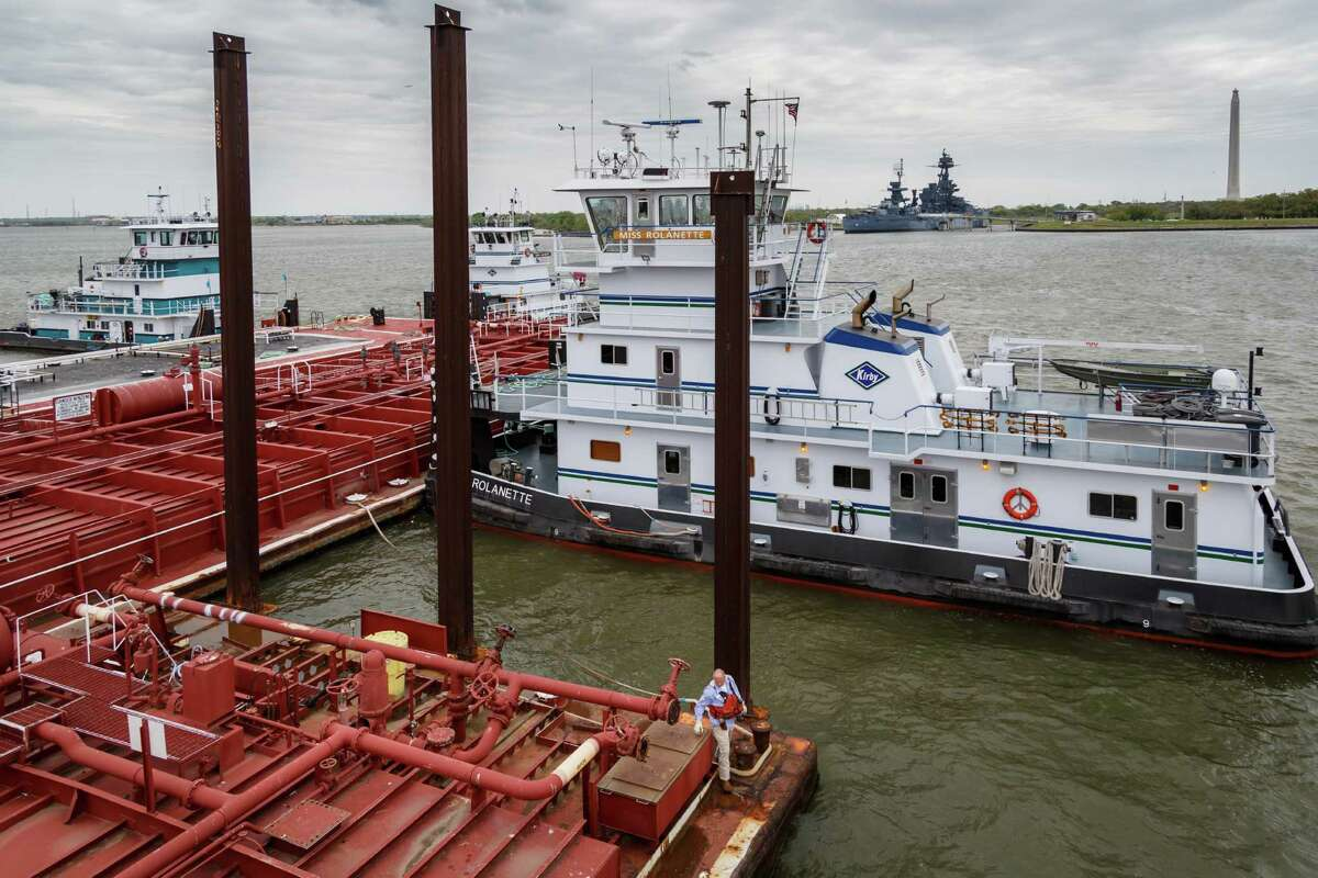 Bill Hearne returns to the towboat after successfully mooring a barge in the Kirby fleet across from the San Jacinto Monument on the Houston Ship Channel, Wednesday, March 26, 2014. Five people typically man the vessel as it transports a barge along the waterways.