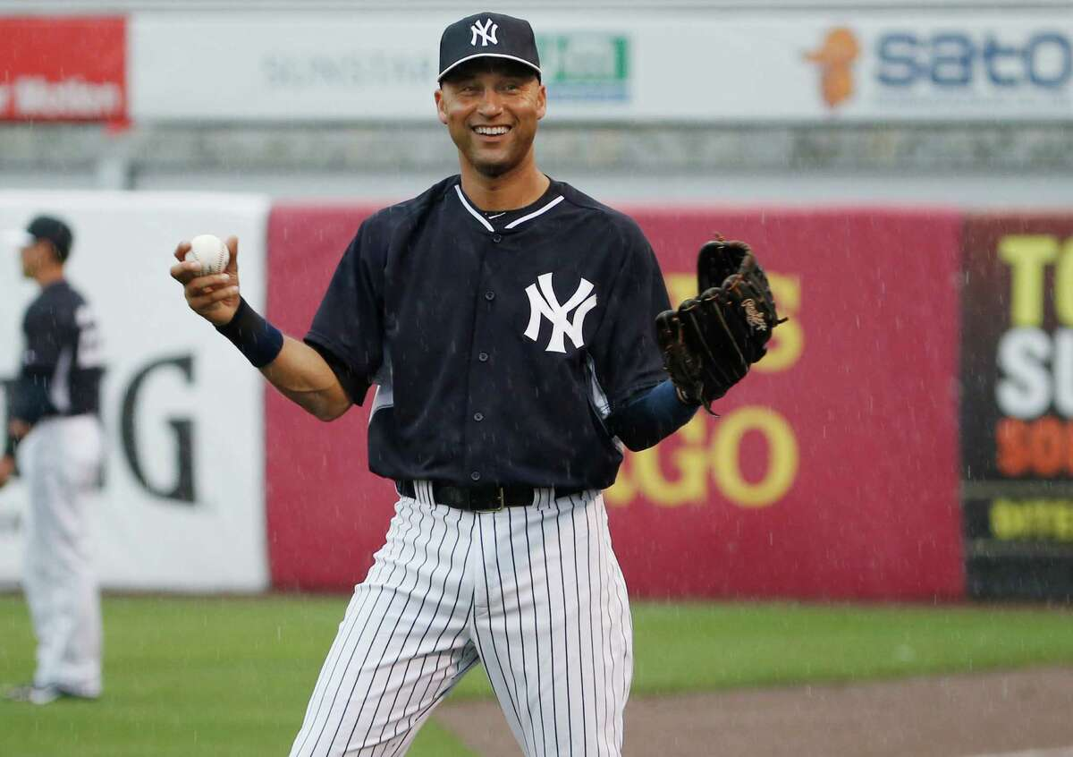 New York Yankees Derek Jeter laughs as he throws in the rain before a spring exhibition baseball game against the Miami Marlins was canceled due to the weather in Tampa, Fla., Saturday, March 29, 2014. (AP Photo/Kathy Willens) ORG XMIT: FLKW108
