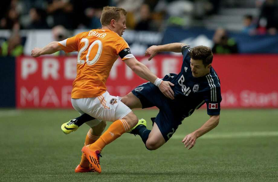 Houston Dynamo's Andrew Driver, left, of England, and Vancouver Whitecaps' Jordan Harvey collide during the first half of an MLS soccer game in Vancouver, British Columbia, Saturday, March 29, 2014. (AP Photo/The Canadian Press, Darryl Dyck) Photo: Darryl Dyck, Associated Press / The Canadian Press