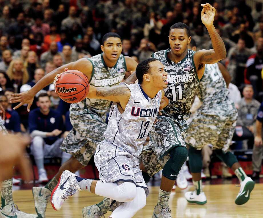 Connecticut guard Shabazz Napier (13) and Michigan State guard Keith Appling (11) challenge for the ball during their NCAA men's basketball game on Saturday, Nov. 10, 2012, on the Ramstein U.S. Air Force Base, in Ramstein, Germany.  (AP Photo/Michael Probst) Photo: Michael Probst, Associated Press / Associated Press