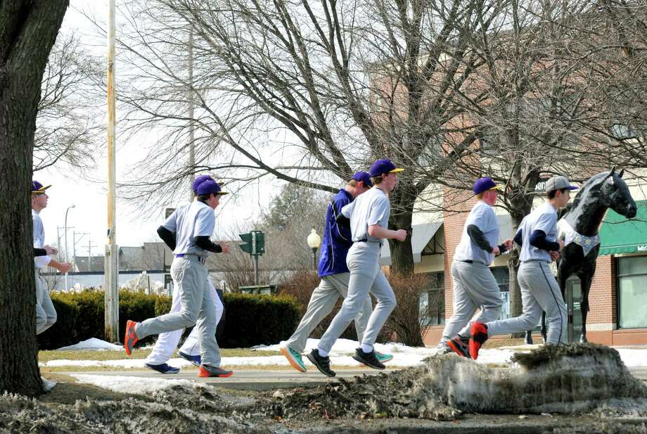 Members of the Saratoga Central Catholic High School junior varsity baseball team take a warm up run down Broadway on Thursday March 27, 2014 in Saratoga Springs, N.Y. (Michael P. Farrell/Times Union) Photo: Michael P. Farrell