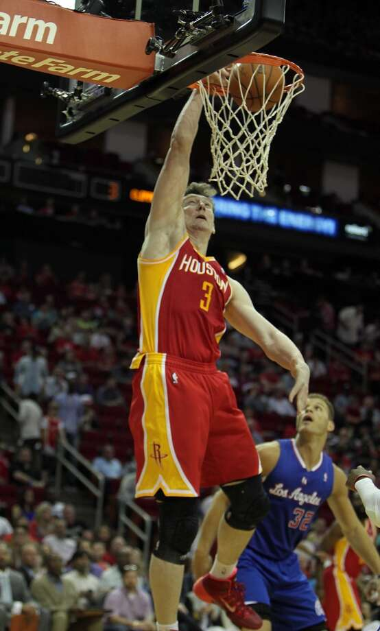 Rockets center Omer Asik left, slam dunks the ball as Clippers forward Blake Griffin right, looks on. Photo: James Nielsen, Houston Chronicle