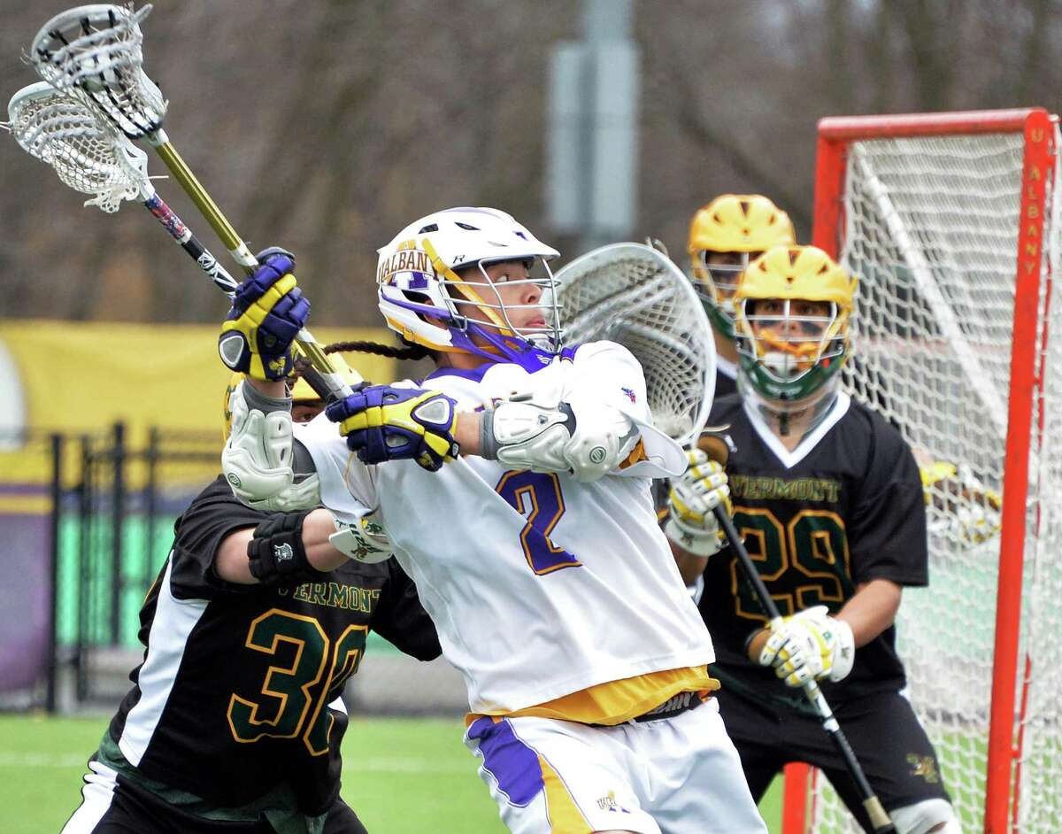 UAlbany's # 2 Miles Thompson, center, takes a shot against Vermont goalie #29 Justin Rosenberg during Saturday's game March 29, 2014, in Albany, NY. (John Carl D'Annibale / Times Union)