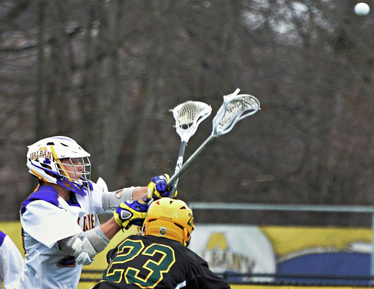 UAlbany's #20 Ryan Feuerstein, left, scores during Saturday's game against Vermont March 29, 2014, in Albany, NY. (John Carl D'Annibale / Times Union)