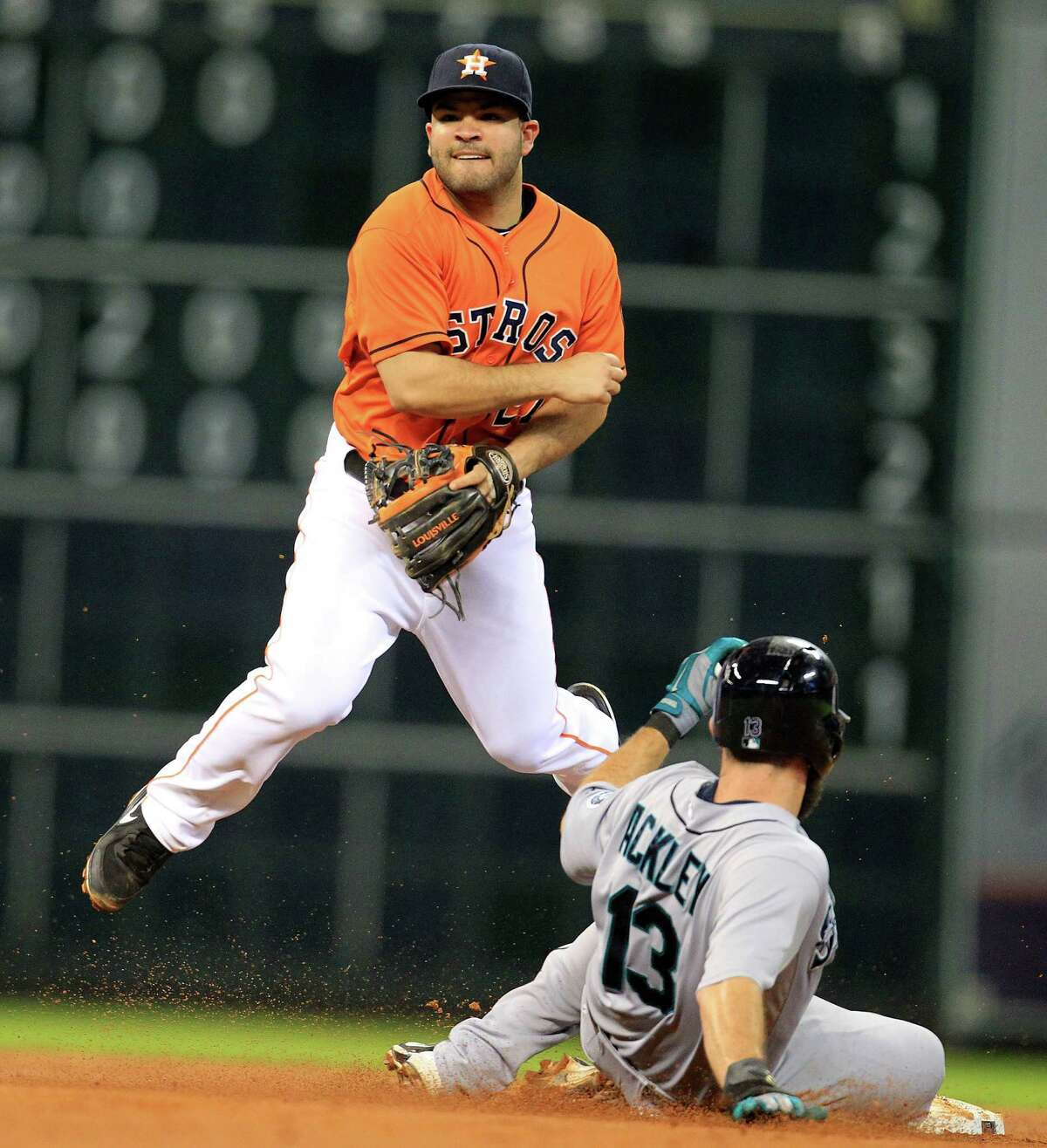 Houston Astros second baseman Jose Altuve (27) tries to get the double play out on on Abraham Almonte after tagging Seattle Mariners second baseman Dustin Ackley (13) out at second during the fourth inning of an MLB game at Minute Maid Park, Friday, Aug. 30, 2013, in Houston. ( Karen Warren / Houston Chronicle )