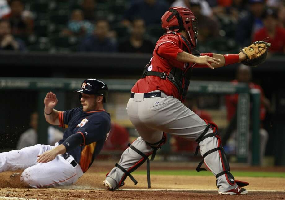 Alex Presley slides into home ahead of the tag by catcher Humberto Sosa. Photo: Melissa Phillip, Houston Chronicle