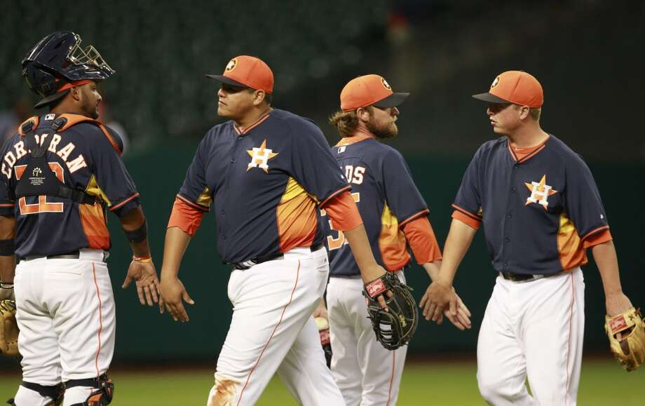 Astros catcher Carlos Corporan, left, Japhet Amador , pitcher Josh Fields, and Matt Dominguez, right, celebrate the win. Photo: Melissa Phillip, Houston Chronicle