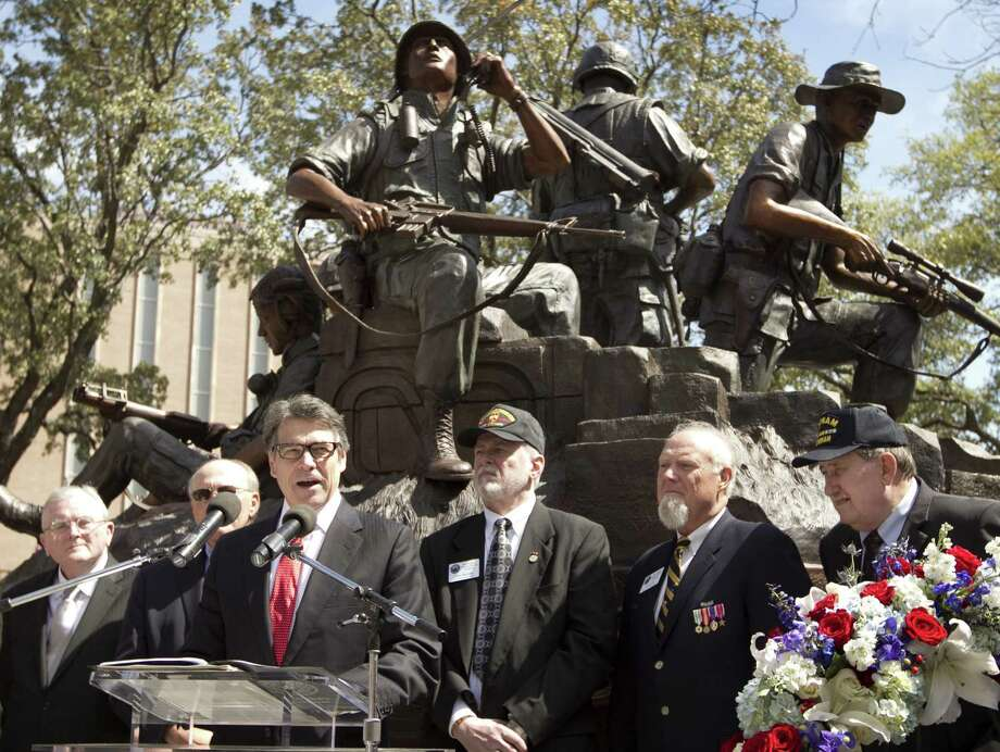 Gov. Rick Perry speaks at the dedication of the Capitol Vietnam Veterans Monument. Dog tags personalized for 3,417 Texans who died in the war or were unaccounted for are inside the monument. Photo: Jay Janner / Austin American-Statesman / Austin American-Statesman