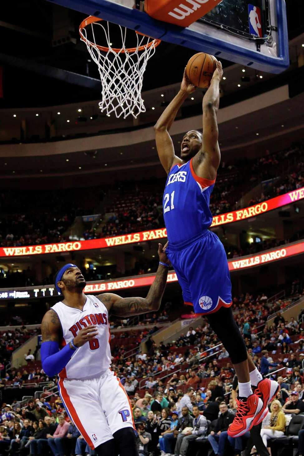 Philadelphia 76ers' Thaddeus Young, right, goes up for a dunk against Detroit Pistons' Josh Smith during the first half of an NBA basketball game on Saturday, March 29, 2014, in Philadelphia. (AP Photo/Matt Slocum) ORG XMIT: PXC101