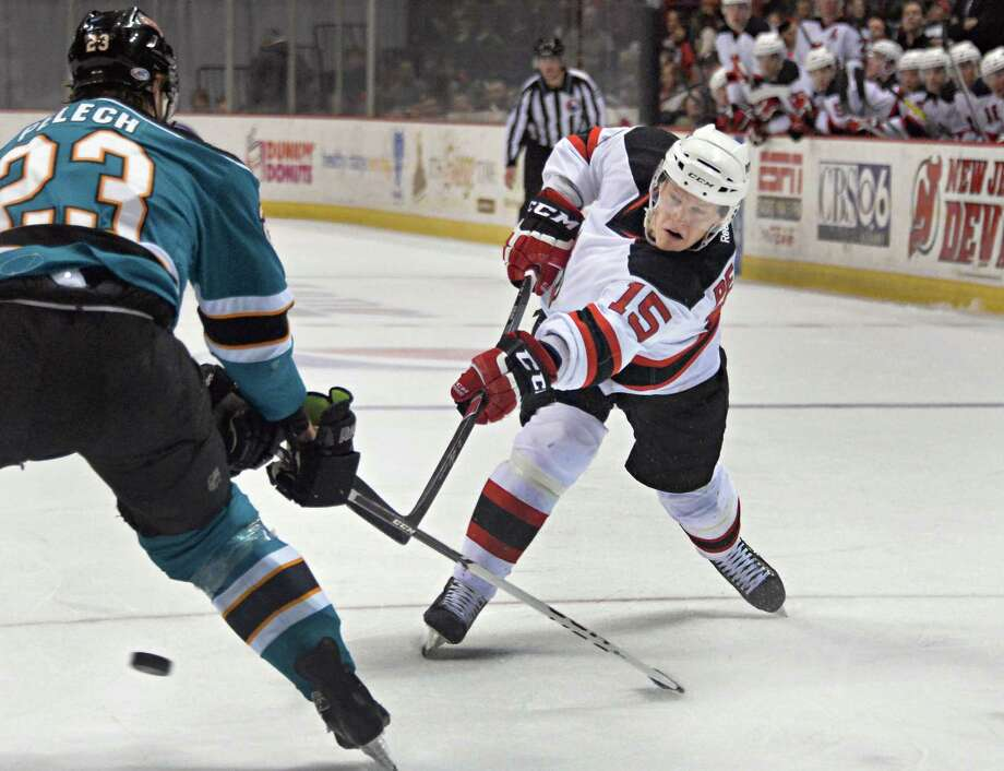 Albany Devils' #15 Harri Pesonen, right, shoots past Worcester Sharks' #23 Matt Pelech during Saturday's game at the Times Union Center March 29, 2014, in Albany, NY.  (John Carl D'Annibale / Times Union) Photo: John Carl D'Annibale / 00026290A