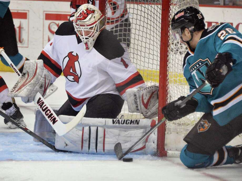 Albany Devils' goalie Keith Kincaid, left, stops a shot by Worcester Sharks' #26 Adam Schmidt  during Saturday's game at the Times Union Center March 29, 2014, in Albany, NY.  (John Carl D'Annibale / Times Union) Photo: John Carl D'Annibale / 00026290A