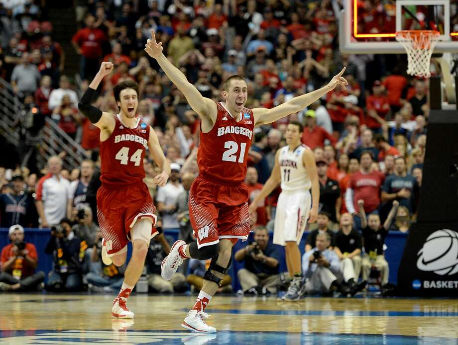 Josh Gasser (21) and Frank Kaminsky, who had a game-high 28 points, celebrate defeating Arizona and Aaron Gordon (11) in the West Regional final. Photo: Harry How, Getty Images