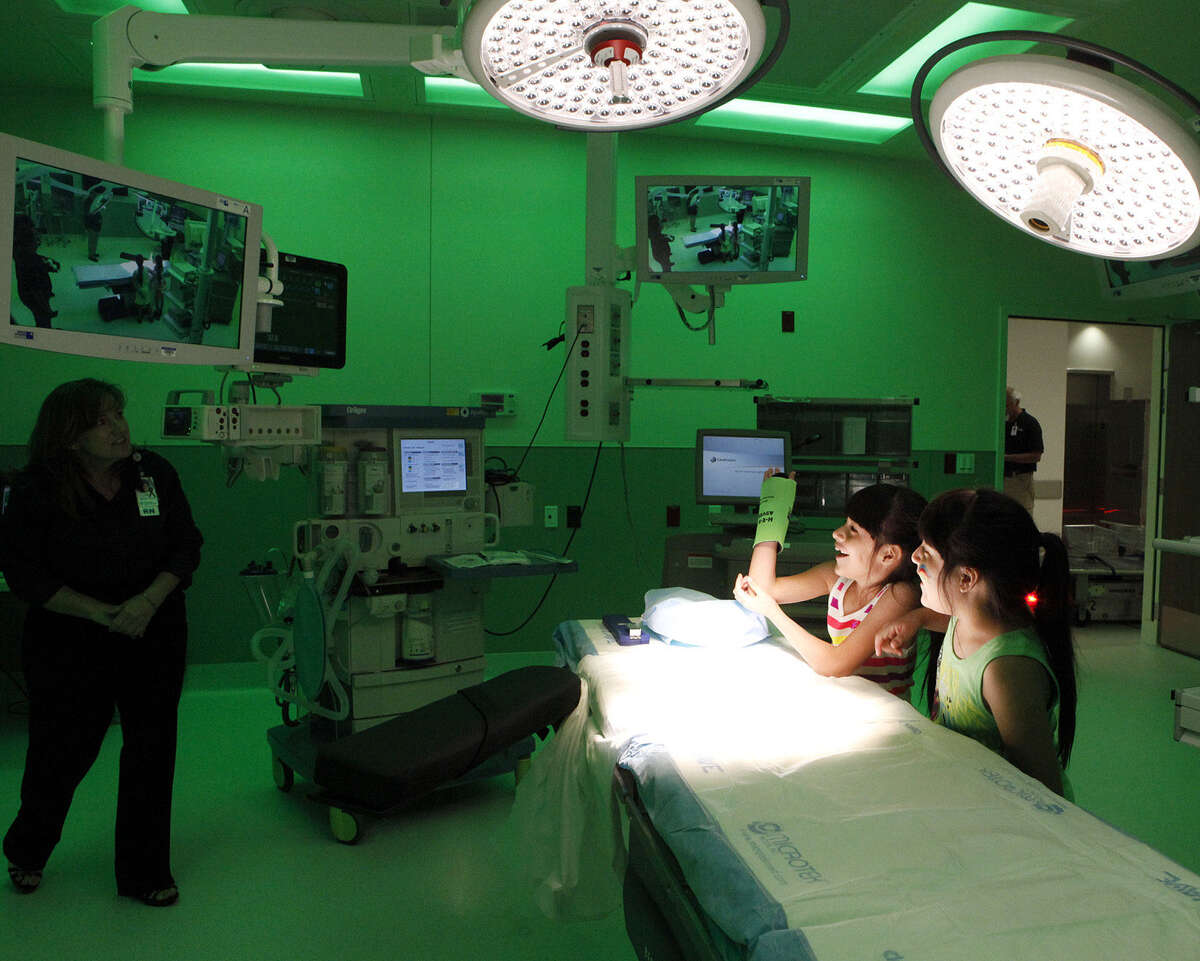 Twins Megan (left) and Alexis Rodriguez, 8, watch themselves on the monitors in one of the operating rooms at University Hospital's Sky Tower and ask questions during a tour.