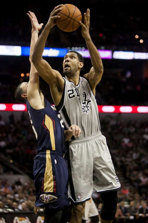 The Spurs' Tim Duncan shoots Saturday March 29, 2014 at the AT&T Center over the Pelicans' Austin Rivers.