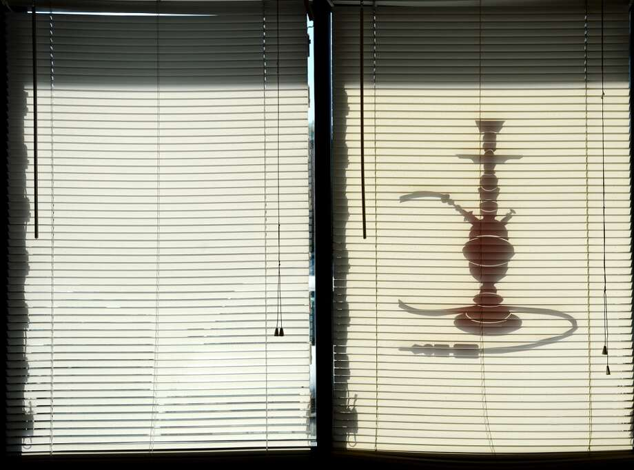 A hookah emblem is seen in silhouette on the windows of the Jerusalem Hookah Cafe's windows Tuesday. The Jerusalem Hookah Cafe has been serving up Middle Eastern cuisine as well as hookahs to the Beaumont area since 2009. Photo taken Tuesday, 3/18/14 Jake Daniels/@JakeD_in_SETX
