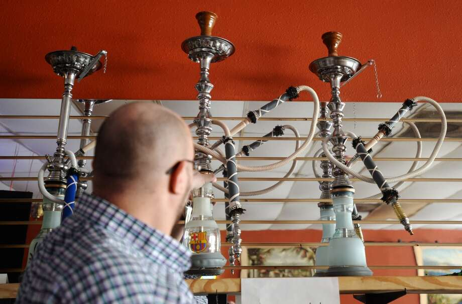 Haytham Abdel places hookahs on a shelf after attaching hoses at the Jerusalem Hookah Cafe on Tuesday. The Jerusalem Hookah Cafe has been serving up Middle Eastern cuisine as well as hookahs to the Beaumont area since 2009. Photo taken Tuesday, 3/18/14 Jake Daniels/@JakeD_in_SETX