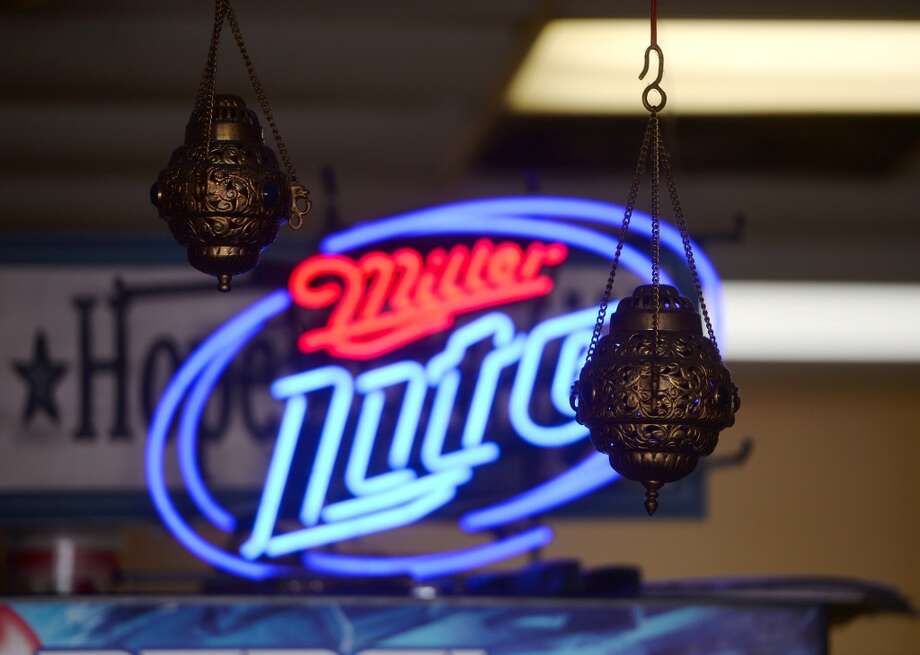 A Miller Lite sign illuminates hanging decorations inside the Jerusalem Hookah Cafe on Tuesday. The Jerusalem Hookah Cafe has been serving up Middle Eastern cuisine as well as hookahs to the Beaumont area since 2009. Photo taken Tuesday, 3/18/14 Jake Daniels/@JakeD_in_SETX